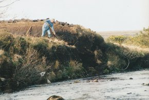 man cutting a turf bank beside the clady river coshclady between gweedore and bunbeg county Donegal